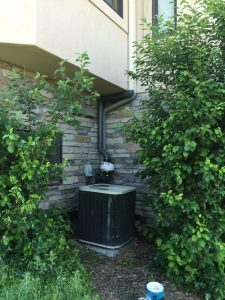 image of a radon mitigation system installed on a home near an AC unit